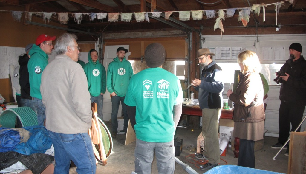 The Clean Energy Service Corps meets in the old garage on a windy, wet day to hear about the Living Building Challenge petals.