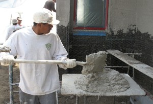 Victor loads the plaster mix ready for application to the wall.