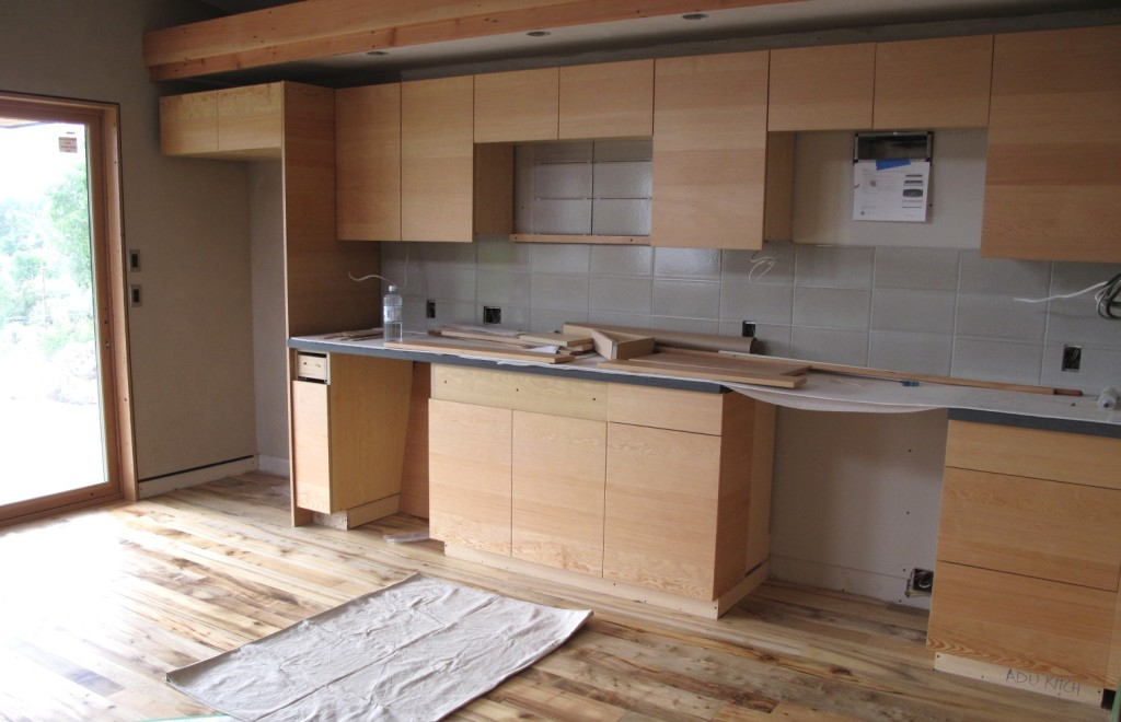 The kitchen area in the ADU with FSC wood cabinets, salvaged myrtlewood flooring, and recycled backsplash tiles.