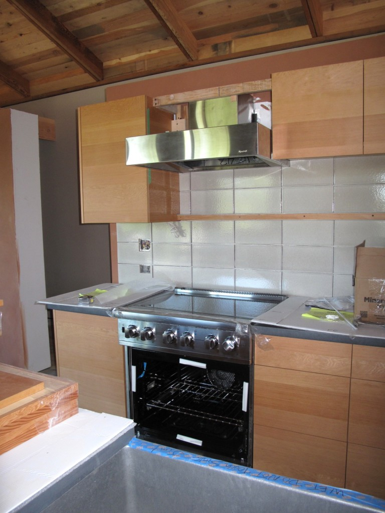 Appliances are in place in the main house kitchen. FSC wood cabinets and recycled material tiles.