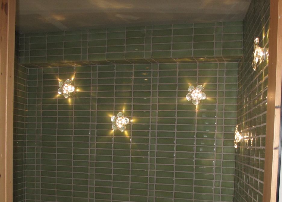 LED flower lights create ambience in the guest bath with light reflecting in the recycled, glass tiles.